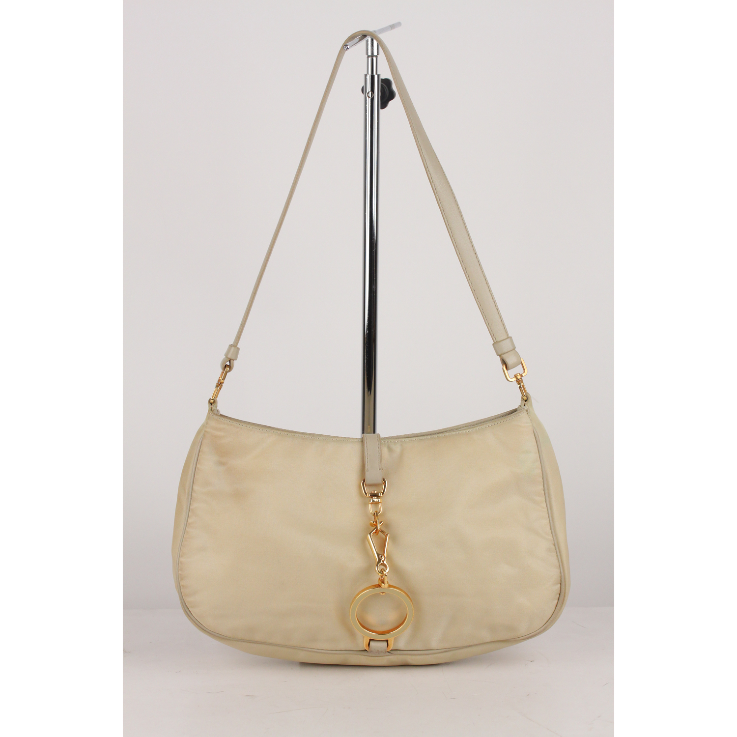 113a5b88ce61 Prada shoulder bag crafted in beige nylon and genuine leather trim. Open  top with fold over strap and clasp closure. 1 side zip pocket inside.